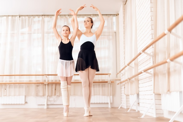 Ballet teacher trains kid at dance school.