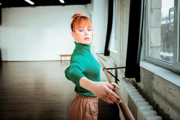 Балетная тренировка. рыжая профессиональная балерина с пучком волос смотрит сосредоточенно, стоя возле балетной стойки