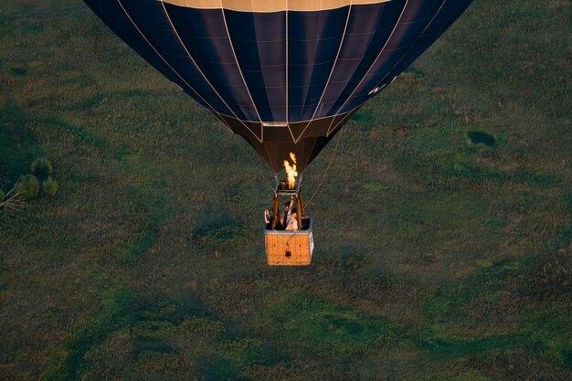 バルーンフェスティバル。空と夕日、自然の静けさを背景にした気球。人々の熱気球が付いているバスケット