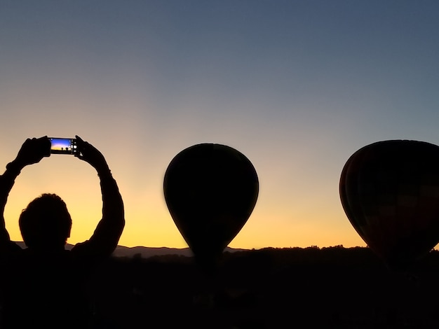 Balloon festival person picturing two balloons in the dark blue sky adirondack queensbury new york