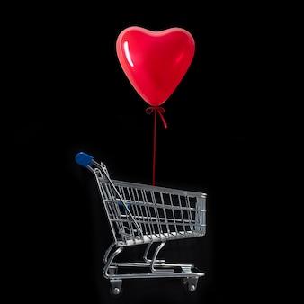 Воздушный шар в форме сердца над тележкой для покупок на черном фоне