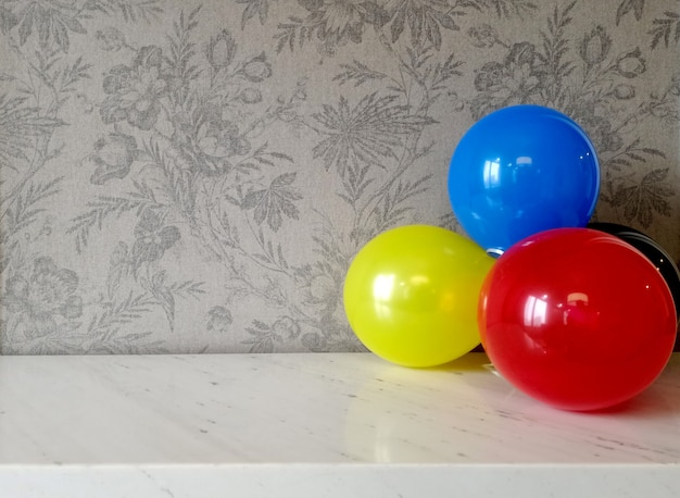 Воздушный шар на мраморном столе с фоном из ткани с цветочным рисунком