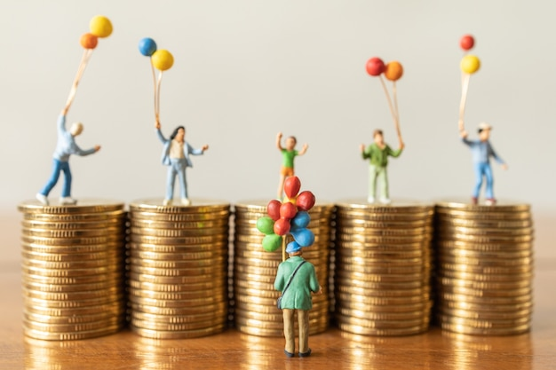 Balloon seller man miniature figures people standing with children on top of stack of coin