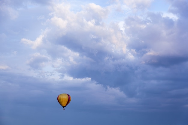 A balloon with a basket filled with hot air flies in the blue sky an air balloon in the blue sky