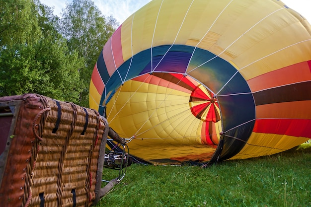 A balloon with a basket lies on the ground equipment for filling the balloon with cold and hot air
