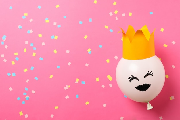 Balloon with happy face on decorated pink background, space for text