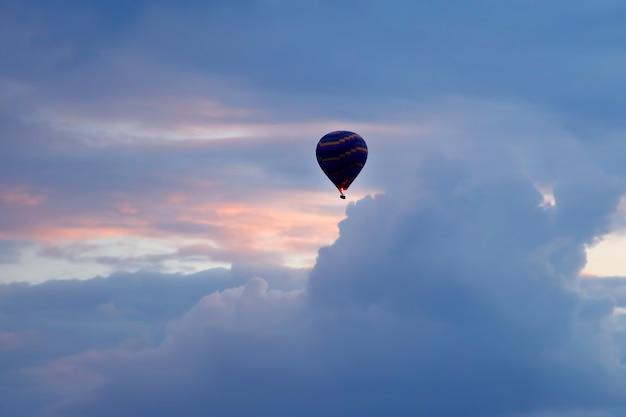 Воздушный шар с людьми, летящими в цветном небе
