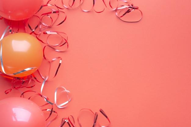풍선 및 빨간 종이 배경에 빛나는 뱀. 파티 장식. 복사 공간