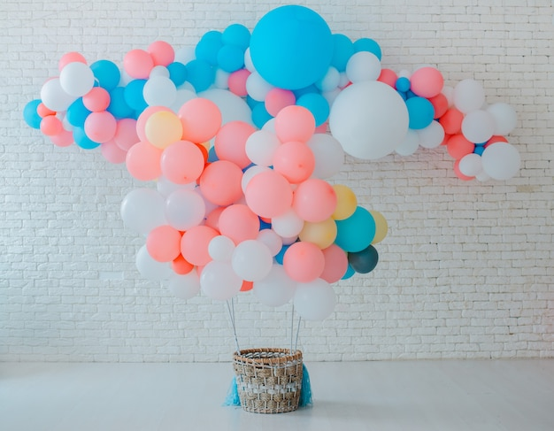 Balloons basket for air flight on white brick with bright blue pink background with free space