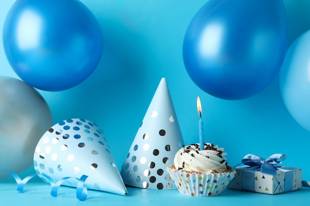 Воздушные шары, шляпы на день рождения, кекс и подарочная коробка на синем фоне, крупным планом