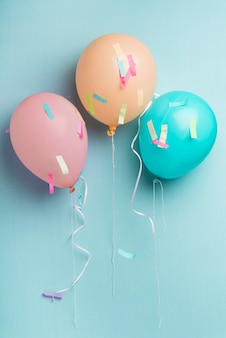 Balloons and confetti on blue background with copy space
