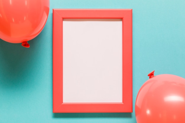 Balloons and empty frame on blue background