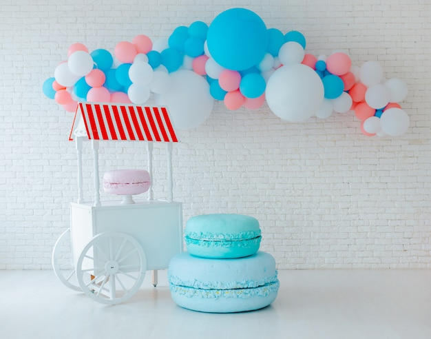 Balloons and ice cream cart on white brick wall