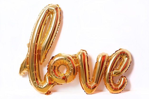 Balloons make people happy, gold balloons word love the word love from the heart on white background
