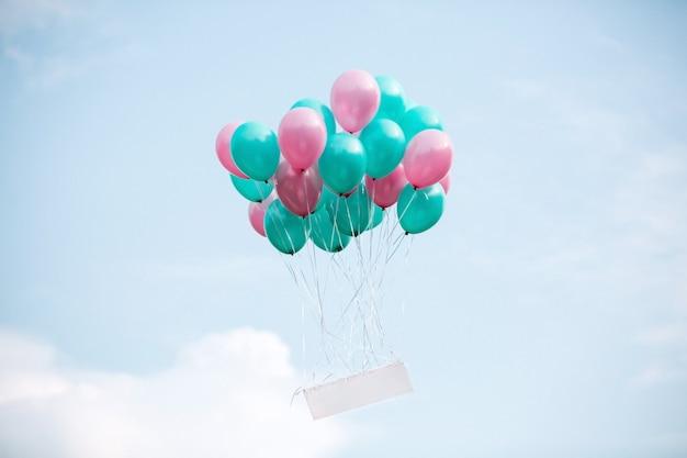 空白のボードで空にヘリウムの風船