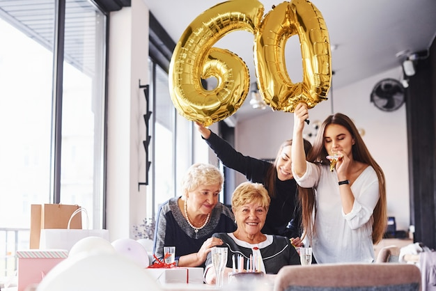 Balloons with number 60. senior woman with family and friends celebrating a birthday indoors.
