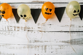 Balloons with pictured faces and black flags hanging on wooden background