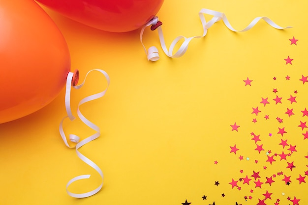Balloons with ribbon and stars on orange background
