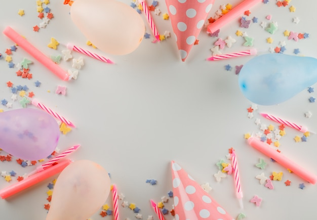 Balloons with sweet sprinkles, candles, party hats on a white table