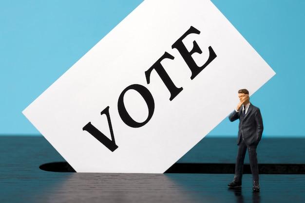 Ballot box with miniature man voter