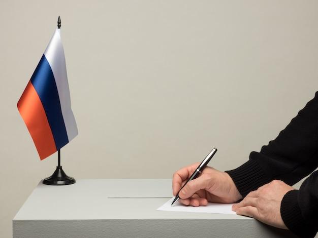 러시아의 국기와 함께 투표함입니다. 2018년 대통령 선거. 투표용지를 던지는 손