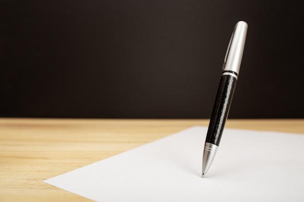Летающая шариковая ручка и лист бумаги на столе. концепция работы, подписи или письма. копировать пространство