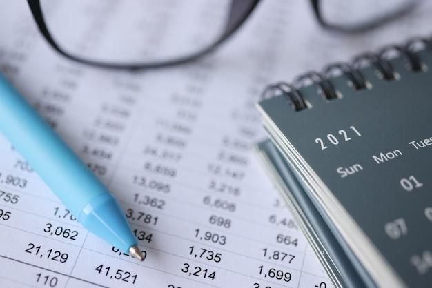 Шариковая ручка и календари, лежащие на документах с номерами крупным планом, документация в бухгалтерском учете