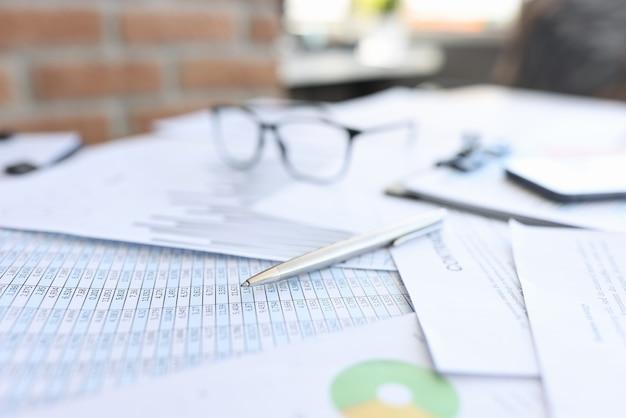 Шариковая ручка и очки, лежащие на документах с крупным планом чисел