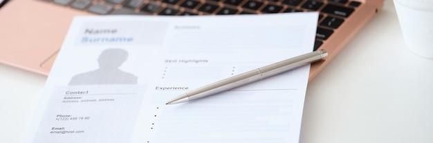 Шариковая ручка, лежащая на документе резюме для работы рядом с ноутбуком крупным планом