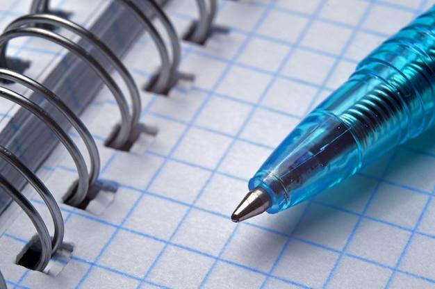 Ballpoint pen on open spiral notebook, macro