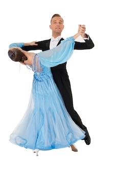 Пара бальных танцев в красном платье танцевальной позы изолирована на черном фоне. чувственные профессиональные танцоры танцуют вальс, танго, слоуфокс и квикстеп. синее платье в чемпионском стиле