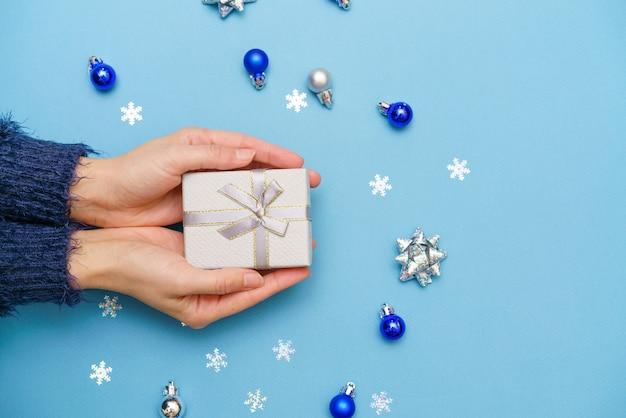 青い背景の冬に暗いセーターを着た女性の手にボールと雪片と新年の贈り物...