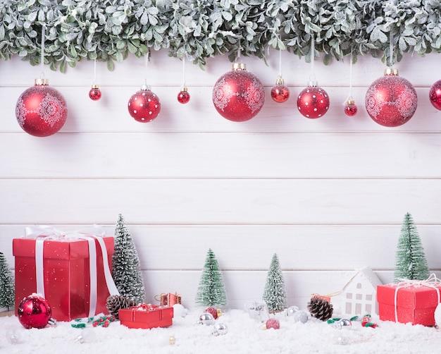 ボールは、コピースペースのある白い木の背景にお祝いのためのメリークリスマスと新年あけましておめでとうございますの装飾の雪をつまらない。