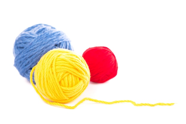 Balls of blue, red and yellow woolen threads on the white background