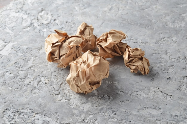 Balls of crumpled old paper on a concrete table. the concept of inappropriate, spent ideas.