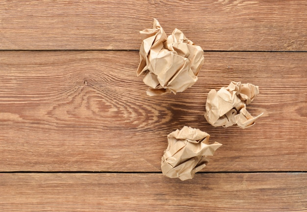 Balls of crumpled old paper on a wooden table. the concept of inappropriate, spent ideas.