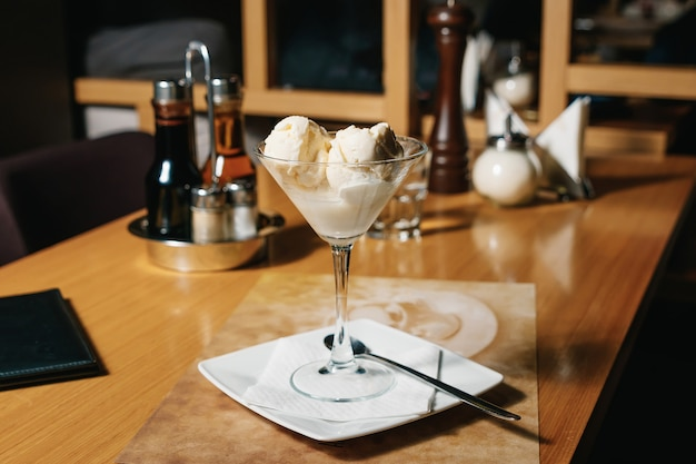Balls of filling ice cream in a martini glass and cointreau liqueur, on a table in a restaurant.