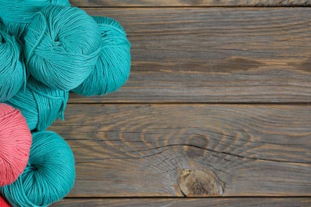 古い木材の背景に明るい毛糸のボール。コピースペース付き。