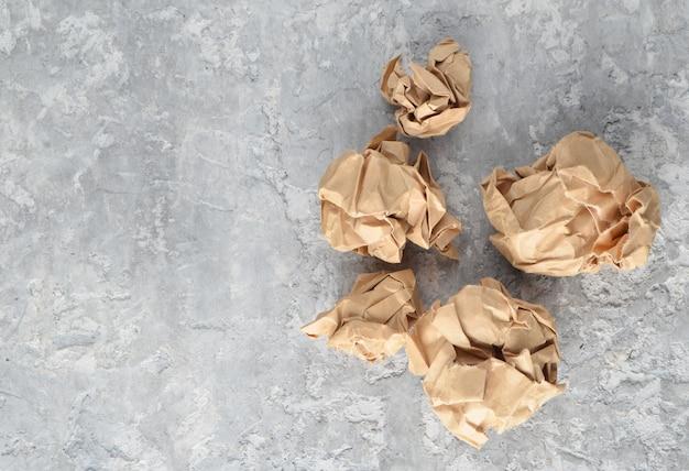 Шарики из мятой старой бумаги на бетонном столе. понятие неуместных, затраченных идей.
