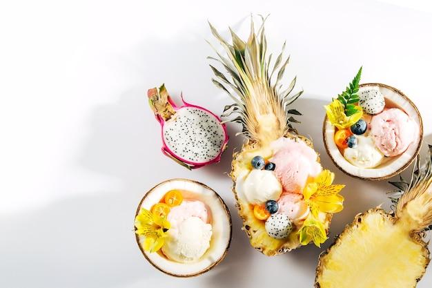 코코넛과 파인애플의 반으로 아이스크림 장식 꽃과 열매의 공. 여름 열 대 개념입니다.