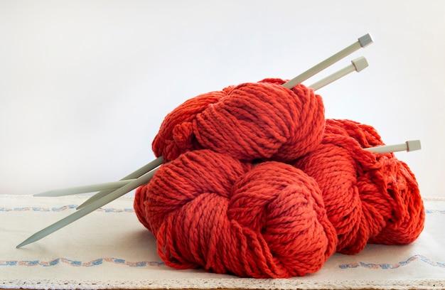 太い赤い羊毛のボールを転がし、編み針