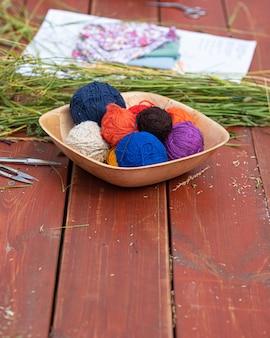 庭の自然の針編みで編む木製のテーブルで編むための羊毛のボール