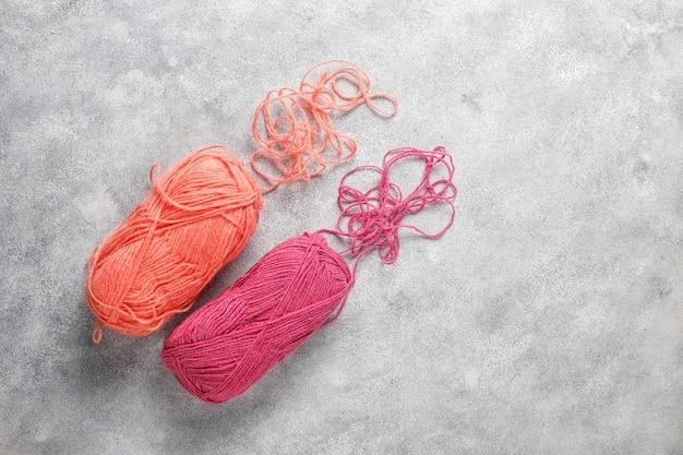 Шарики пряжи разных цветов спицами.