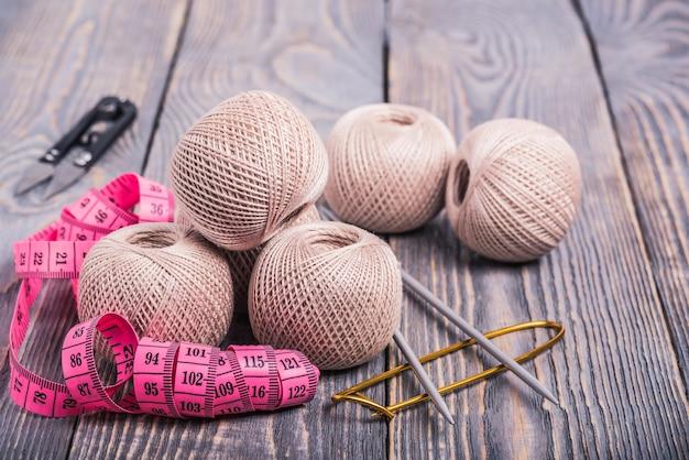 木の表面に毛糸のボール、編み針、巻尺。