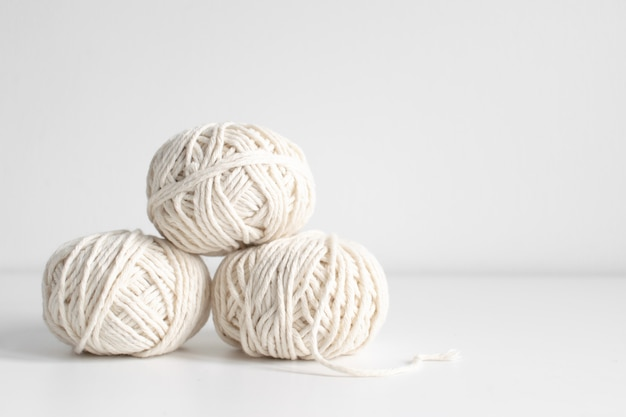 Balls of white yarn on a white wall background. threads of wool boho image. space for text. good for macrame and handicrafts banners and advertisement