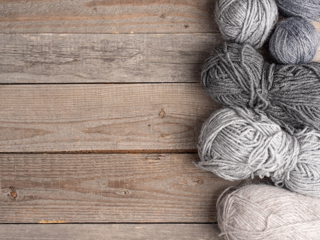 Balls of wool of different colors and sizes lie on a natural wooden surface. top view. copy space.