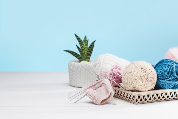 Balls of wool on white wooden background