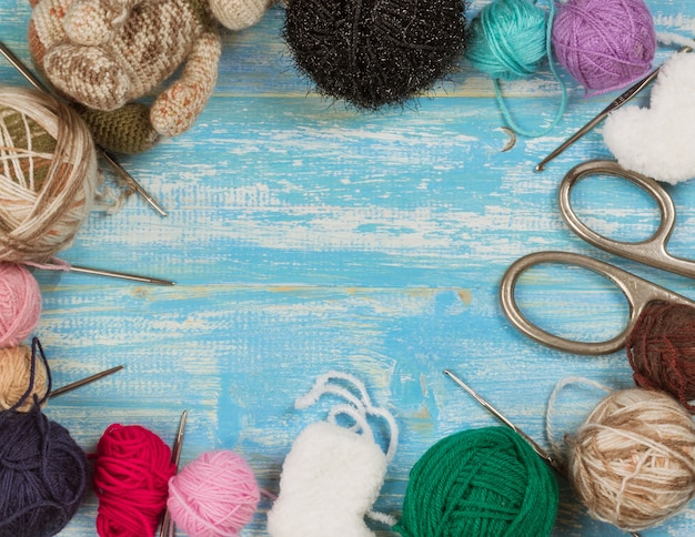 Balls of wool yarn, scissors and knitting needles on a wooden table.