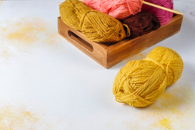 Balls of yarn in different colors with knitting needles.