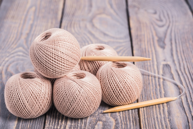 Balls of yarn and knitting needles for knitting on a wooden background.